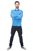 Full length portrait of a confident young man with beard standing on isolated white background with arms crossed