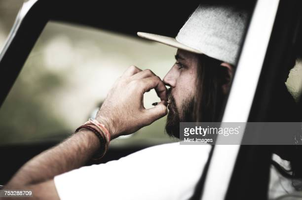Bearded young man wearing baseball cap sitting in a car, smoking cigarette.