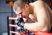 Side view portrait of sweaty exhausted shirtless boxer resting, catching breath after hard fight in boxing ring