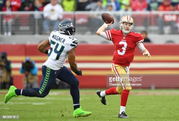 J Beathard of the San Francisco 49ers gets his pass off under pressure from Bobby Wagner of the Seattle Seahawks during their NFL football game at...