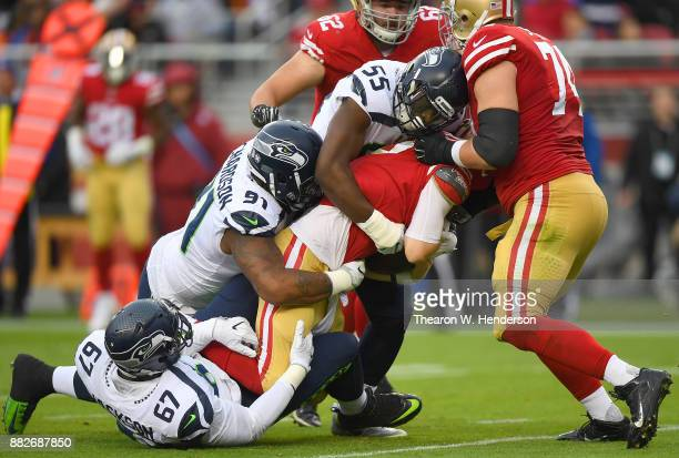 J Beathard of the San Francisco 49ers gets sacked by Sheldon Richardson Frank Clark and Branden Jackson of the Seattle Seahawks during their NFL...