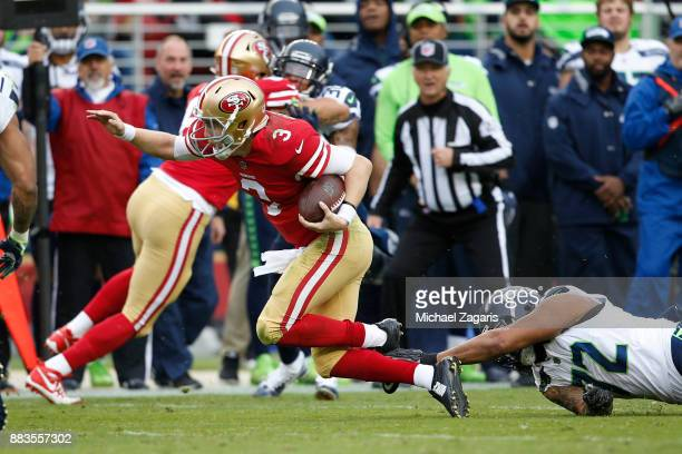 J Beathard of the San Francisco 49ers gets tripped up by Michael Bennett of the Seattle Seahawks during the game at Levi's Stadium on November 26...