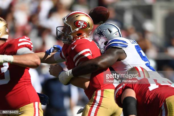J Beathard of the San Francisco 49ers is stripped of the ball by DeMarcus Lawrence of the Dallas Cowboys during their NFL game at Levi's Stadium on...