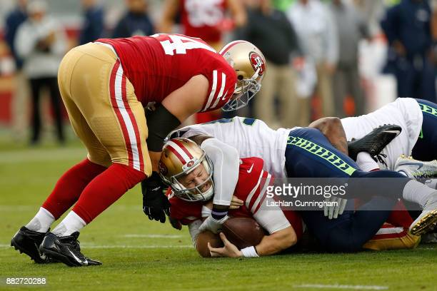 J Beathard of the San Francisco 49ers is tackled by Frank Clark of the Seattle Seahawks at Levi's Stadium on November 26 2017 in Santa Clara...