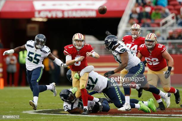 J Beathard of the San Francisco 49ers is tackled by Michael Bennett and Nazair Jones of the Seattle Seahawks at Levi's Stadium on November 26 2017 in...