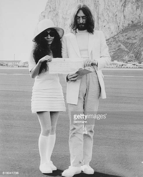 Beatle John Lennon and his bride Japaneseborn Yoko Ono hold the marriage certificate following their registry office wedding here on March 21st...