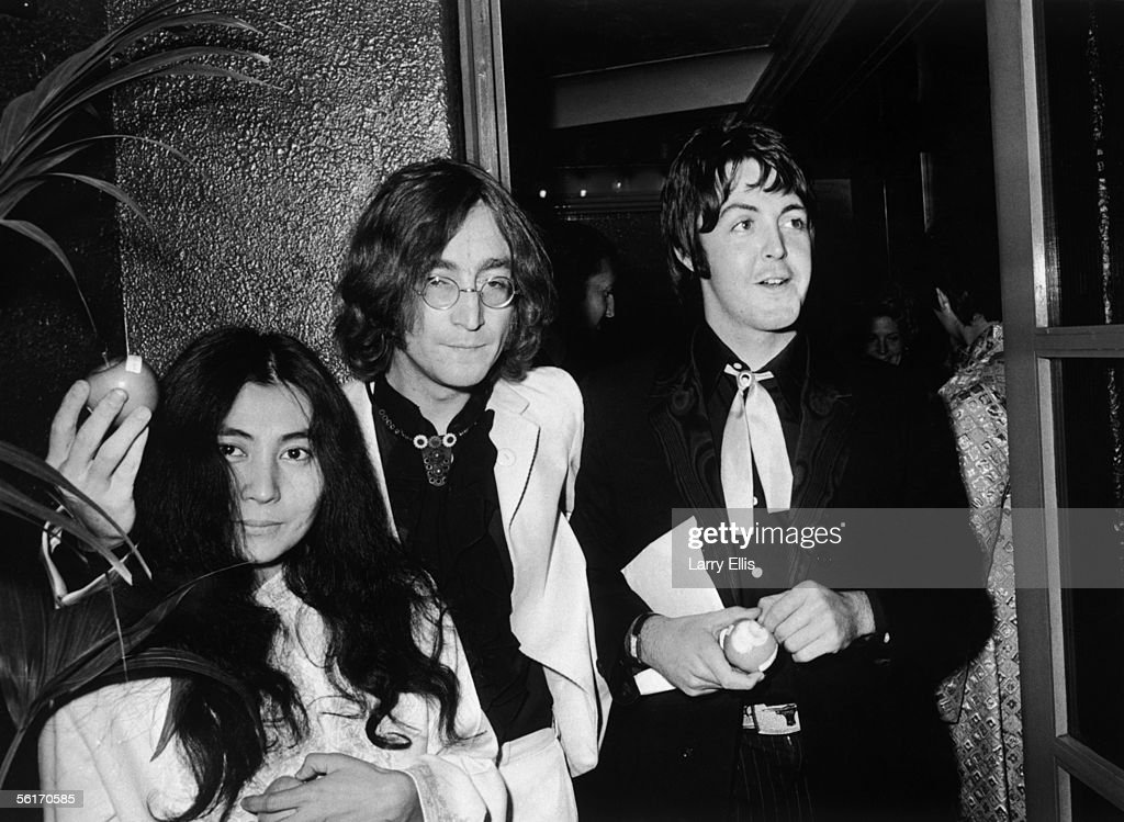 Beatle John Lennon (1940 - 1980) and his Japanese girlfriend Yoko Ono with Beatle Paul McCartney (right), at the premiere of the new Beatles film 'Yellow Submarine' at the London Pavilion, 18th July 1968. John and Paul hold apples, the symbol of their newly formed company, Apple Corps. Thousands of Beatle fans brought traffic to a standstill in Piccadilly Circus as they waited to see the group arrive at the premiere.