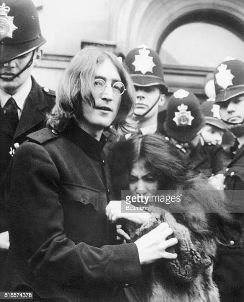 Beatle John Lennon holds his girlfriend artist Yoko Ono as they leave a London court hearing after facing charges of possessing marijuana and...