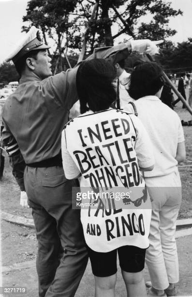 Beatles fan in Tokyo wearing a customised shirt is directed by a policeman