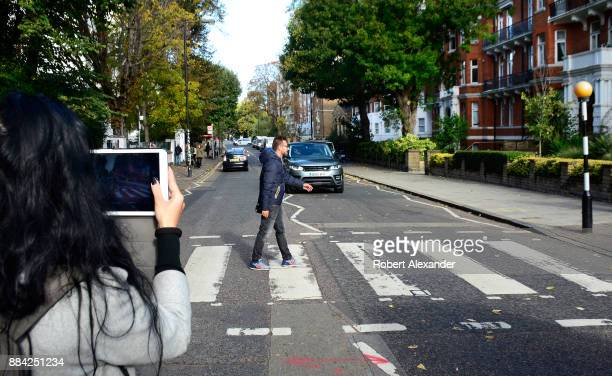 Beatles fan is photographed as he walks across Abby Road in London England recreating the famous 1969 Beatles 'Abby Road' album cover photograph...