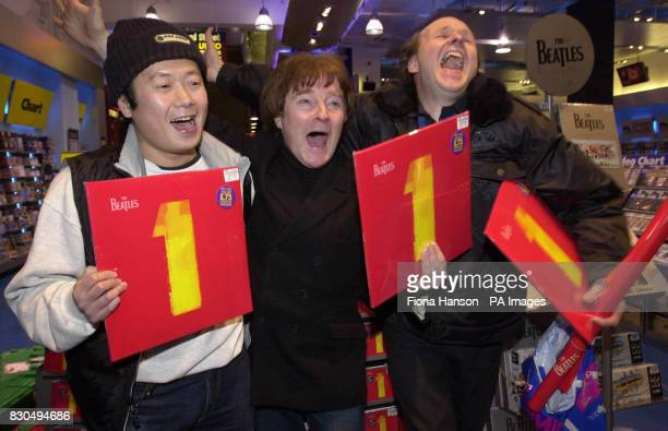 Beatles fans Naoto Ito Alan Harrington and Geoff Evans show their pleasure in HMV in Oxford Street London at one minute past midnight of being one of...