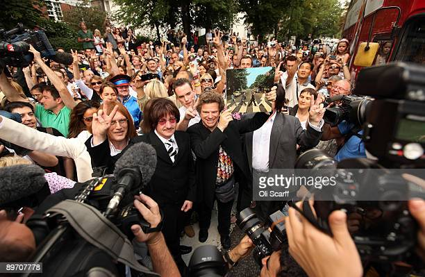 Beatles fans surround Richard Porter owner of the Beatles Coffee Shop as he holds a copy of the Abbey Road LP aloft on the Abbey Road pedestrian...
