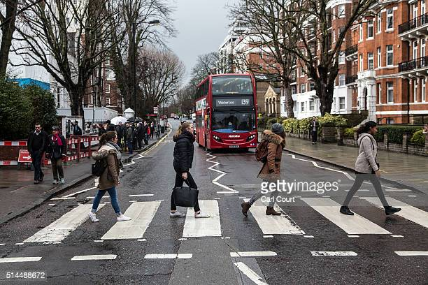 Beatles fans walk across the famous Abbey Road zebra crossing after paying tribute at nearby Abbey Road Studios to Beatles producer George Martin on...