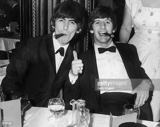 Beatles George Harrison and Ringo Starr smoke cigars in tuxedos after the presentation of the Carl Allen Awards March 23 1964 in London It was...