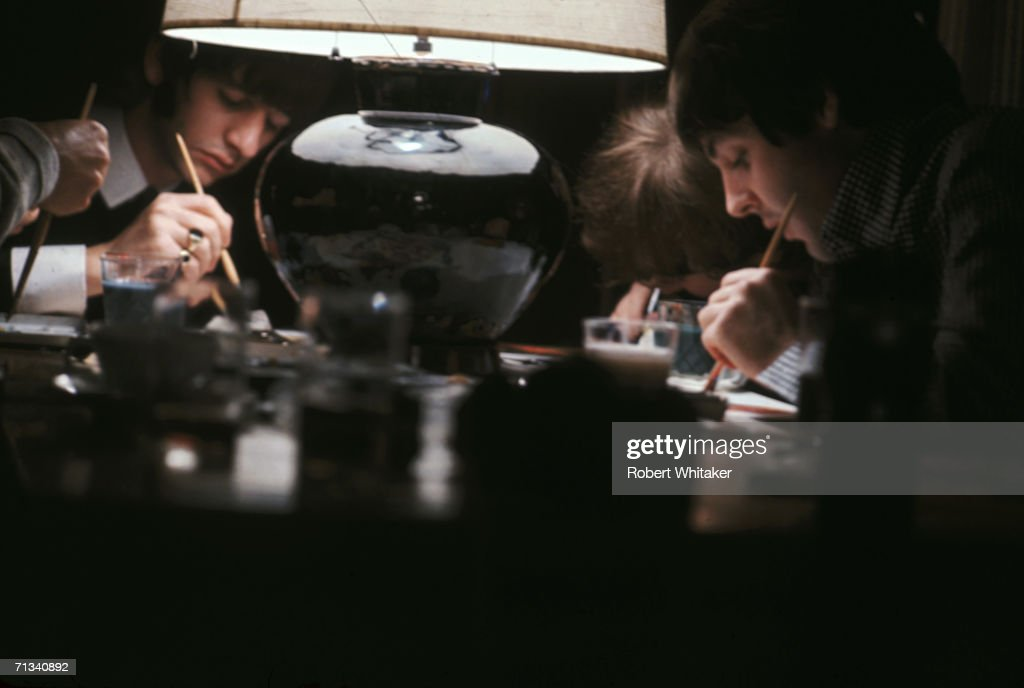Beatles George Harrison (hidden), Ringo Starr, John Lennon and Paul McCartney, busy completing their only known collaborative artwork, 'Images of a Woman' at the Tokyo Hilton, Japan during their tour of Asia, 1966.