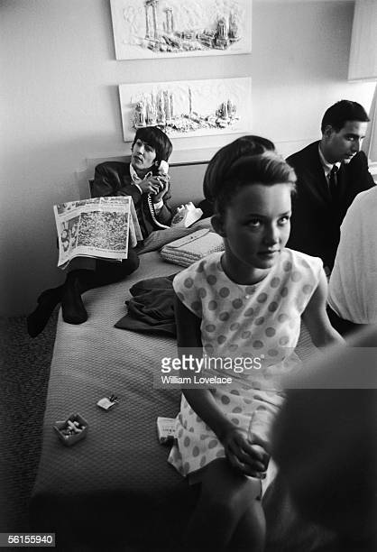Beatles guitarist George Harrison on the telephone in a hotel room during the groups tour of America August 1964 He is reading an article about...