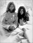 Beatles member John Lennon and his wife Yoko Ono receive journalists 25 March 1969 in the bedroom of the Hilton hotel suite in Amsterdam during their...