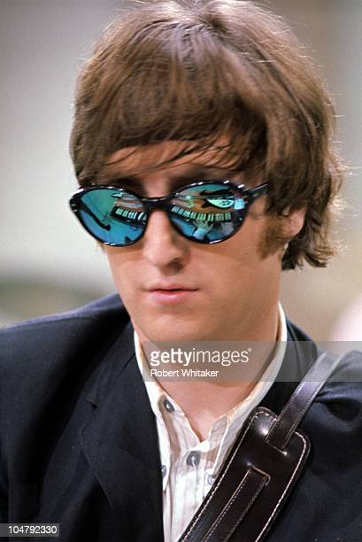 Beatles singer and songwriter John Lennon wearing mirrored sunglasses in which his organ keyboard and Rickenbacker guitar are reflected August 1965