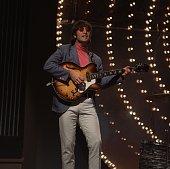 Beatles singer songwriter and guitarist John Lennon performing against a lit backdrop