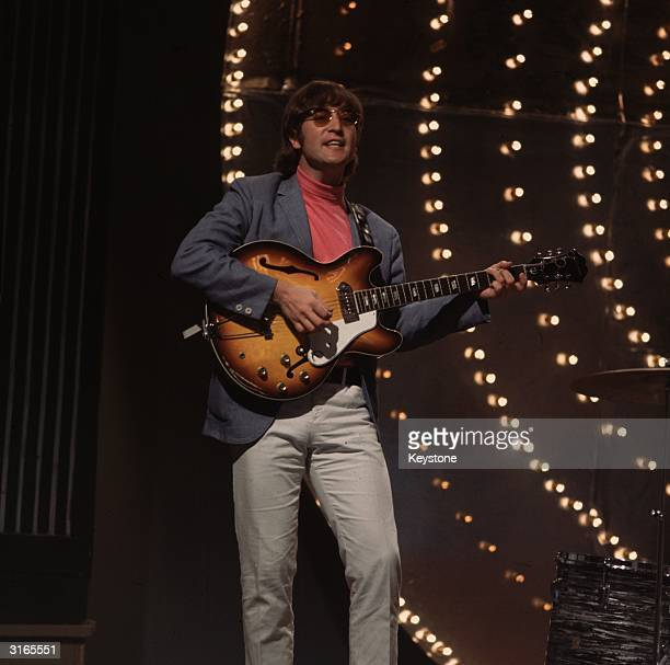 Beatles singer songwriter and guitarist John Lennon performing against a lit backdrop