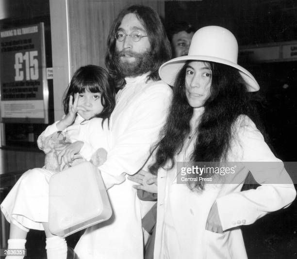 Beatles singer songwriter and guitarist John Lennon with his wife Yoko Ono at London's Heathrow airport before flying to the Bahamas to stage a seven...