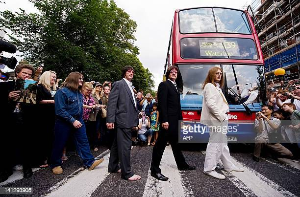 A Beatles tribute band pose for photographs as they walk on the zebra crossing used in the photoshoot for the Beatles album Abbey Road outside the...