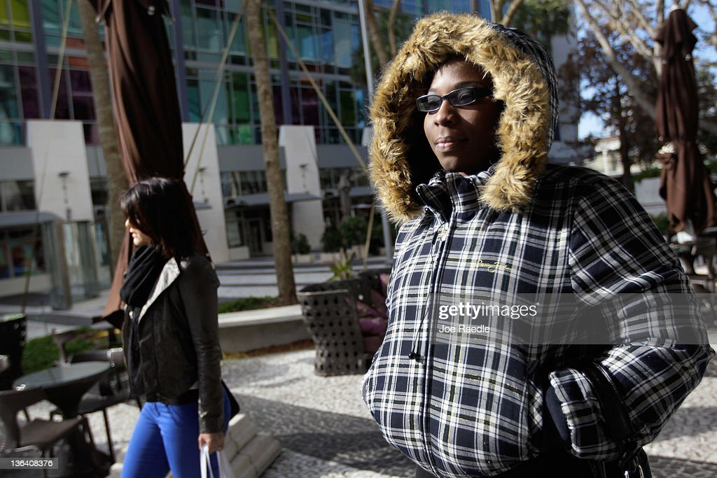 Beatrice Alabre bundles up against the cool weather as she walks along Lincoln road mall on January 4, 2012 in Miami Beach, Florida. South Florida experienced one of the coolest days of the winter season last night but temperatures are expected to warm up.