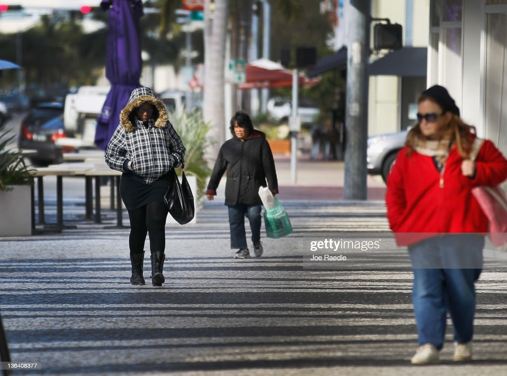 Beatrice Alabre (L) bundles up against the cool weather as she walks along Lincoln road mall on January 4, 2012 in Miami Beach, Florida. South Florida experienced one of the coolest days of the winter season last night but temperatures are expected to warm up.