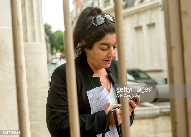 Beatrice Huret the widow of a French police officer and a former activist of the farright Front National party looks at her phone as she arrives at...