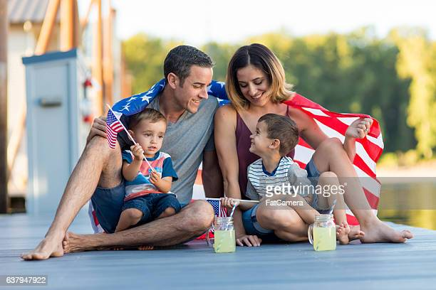 A beatufiul family draped in an american flag laughing