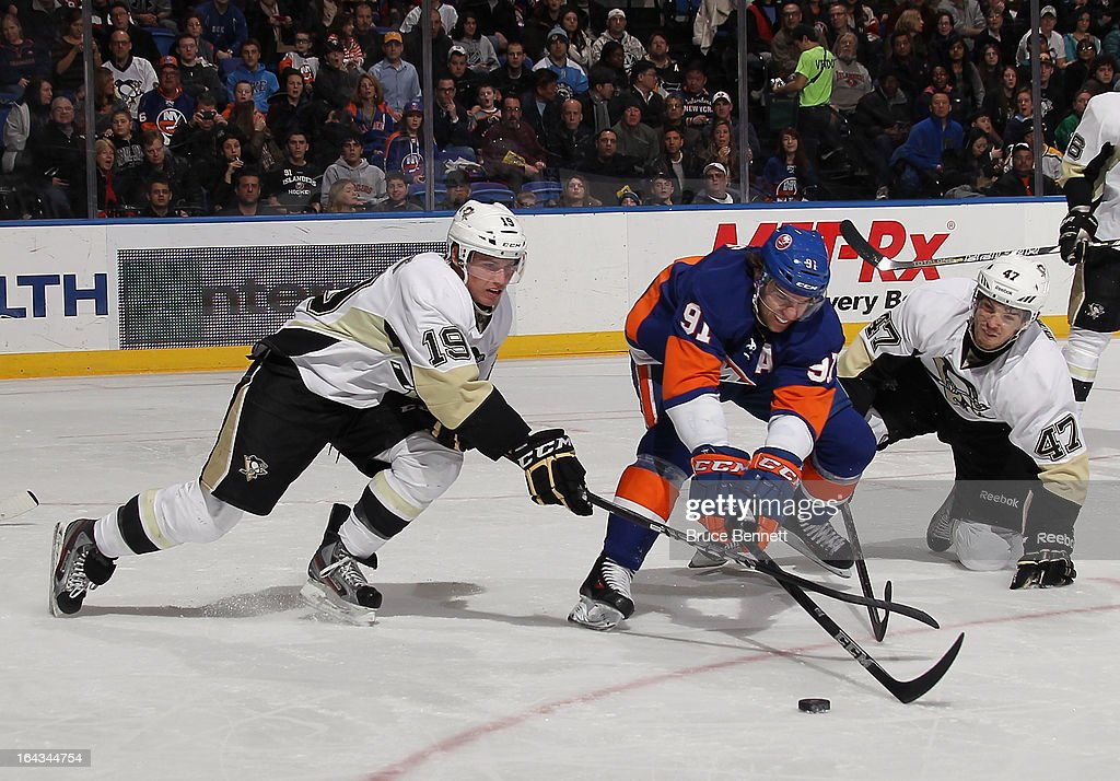 Beau Bennett #19 and Simon Despres #47 of the Pittsburgh Penguins defend against John Tavares #91 of the New York Islanders at Nassau Veterans Memorial Coliseum on March 22, 2013 in Uniondale, New York.