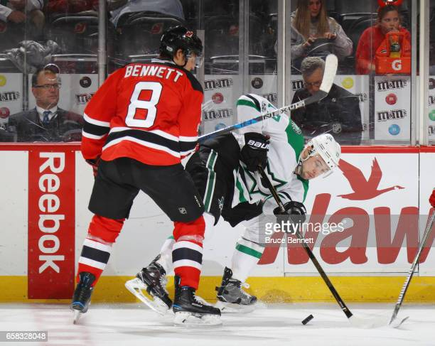 Beau Bennett of the New Jersey Devils checks Devin Shore of the Dallas Stars at the Prudential Center on March 26 2017 in Newark New Jersey The Stars...
