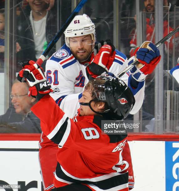 Beau Bennett of the New Jersey Devils is hit Rick Nash of the New York Rangers during the first period at the Prudential Center on March 21 2017 in...