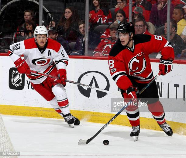 Beau Bennett of the New Jersey Devils takes the puck as Derek Ryan of the Carolina Hurricanes defends on March 25 2017 at Prudential Center in Newark...