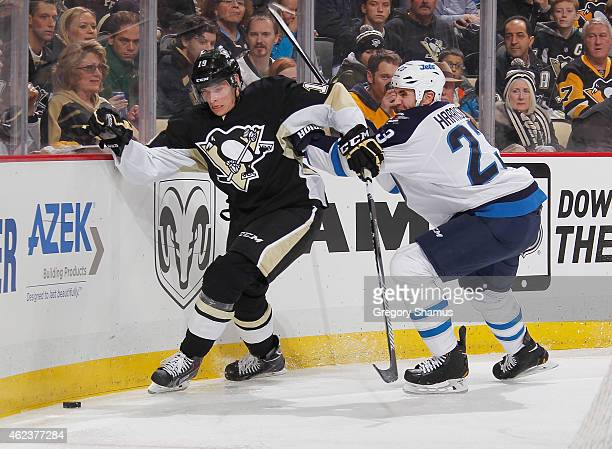 Beau Bennett of the Pittsburgh Penguins and Jay Harrison of the Winnipeg Jets battle for the loose puck at Consol Energy Center on January 27 2015 in...