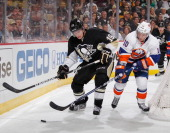 Beau Bennett of the Pittsburgh Penguins battles for the puck against Keith Aucoin of the New York Islanders in Game One of the Eastern Conference...