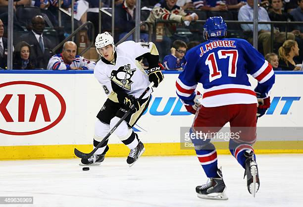 Beau Bennett of the Pittsburgh Penguins controls the puck against John Moore of the New York Rangers in the third period during Game Six of the...