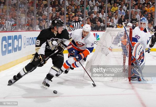 Beau Bennett of the Pittsburgh Penguins moves the puck in front of the defense of Marty Reasoner of the New York Islanders in Game One of the Eastern...