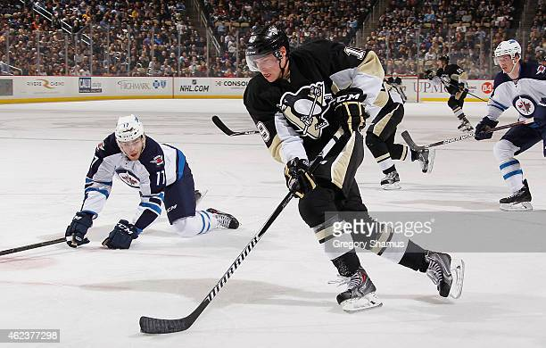 Beau Bennett of the Pittsburgh Penguins moves the puck up ice in front of Adam Lowry of the Winnipeg Jets at Consol Energy Center on January 27 2015...