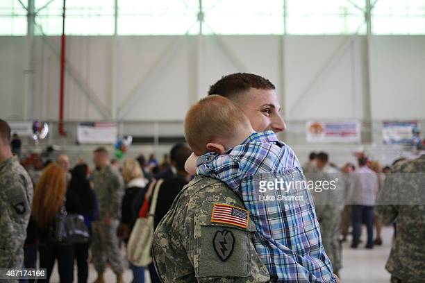 Beau Depalo hugs his father SSgt Michael Depalo of the US Army's 101st Airborne Division during a homecoming ceremony at Campbell Army Airfield on...