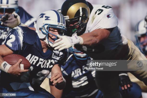 Beau Morgan quarterback of the Air Force Falcons is tackled by line backer Karl Ballard of the Colorado State Rams during their NCAA Division IA...