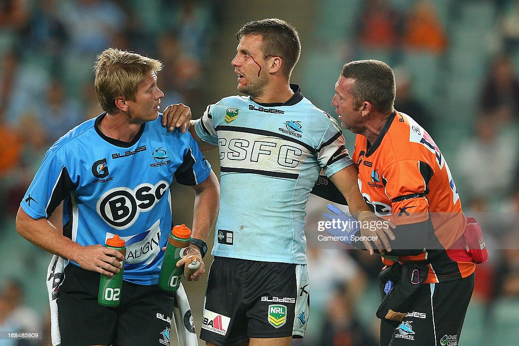 Beau Ryan of the Sharks is assisted after a high tackle during the round nine NRL match between the Wests Tigers and the Cronulla Sharks at Allianz Stadium on May 10, 2013 in Sydney, Australia.
