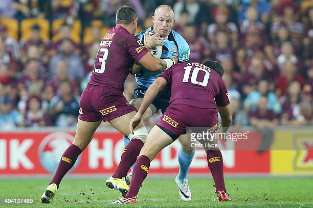 Beau Scott of the Blues is tackled by Corey Parker and Nate Myles of the Maroons during game one of the State of Origin series between the Queensland...