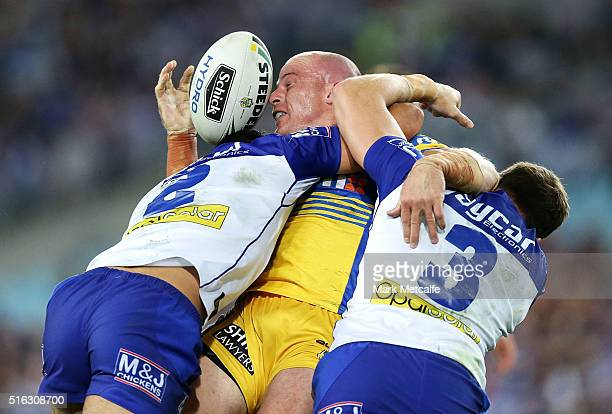 Beau Scott of the Eels is tackled by Curtis Rona and Josh Morris of the Bulldogs during the round three NRL match between the Canterbury Bulldogs and...