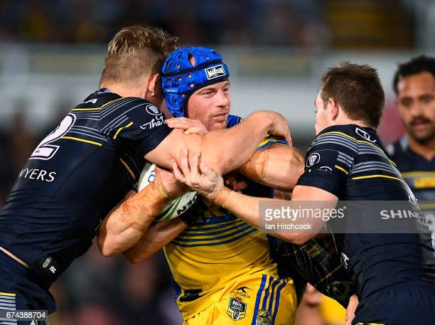 Beau Scott of the Eels is tackled by Michael Morgan and Coen Hess of the Cowboys during the round nine NRL match between the North Queensland Cowboys...