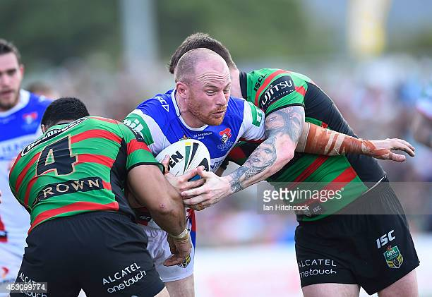 Beau Scott of the Knights is tackled by Chrs McQueen and Kirisome Auva'a of the Rabbitohs during the round 21 NRL match between the South Sydney...