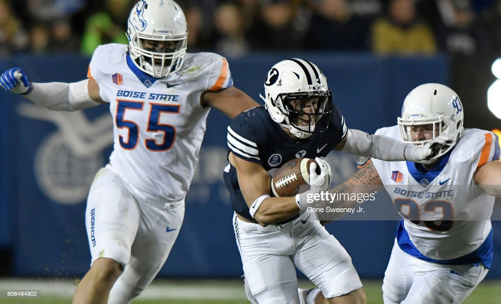 Beau Tanner #33 of the Brigham Young Cougars tries to avoid David Moa #55 and Chase Hatada #93 of the Boise State Broncos during the first half at LaVell Edwards Stadium on October 6, 2017 in Provo, Utah.
