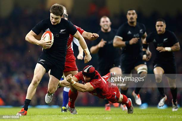 CARDIFF WALES NOVEMBER Beauden Barrett of the All Blacks breaks the tackle of Leigh Halfpenny of Wales during the Intenational match between Wales...