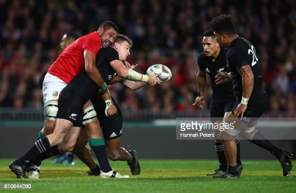 Beauden Barrett of the All Blacks offloads as he is tackled by Taulupe Faletau of the Lions during the third test match between the New Zealand All...
