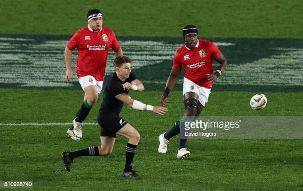 Beauden Barrett of the All Blacks passes the ball watched by Jamie George and Maro Itoje during the Test match between the New Zealand All Blacks and...